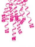 Las cintas rosadas que cuelgan el frente rematan en el fondo blanco Fotografía de archivo libre de regalías