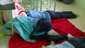 Las colegialas adolescentes en Tailandia duermen en el piso de la sala de clase Foto de archivo
