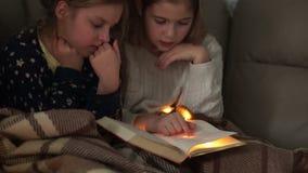Las colegialas están aprendiendo lecciones en cama por la tarde, cubierta con una manta almacen de video