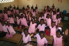 Las colegialas haitianas y los muchachos de la guardería joven muestran las pulseras de la amistad en sala de clase de la escuela Imagen de archivo libre de regalías