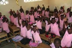 Las colegialas haitianas y los muchachos de la guardería joven muestran las pulseras de la amistad en sala de clase de la escuela Imágenes de archivo libres de regalías