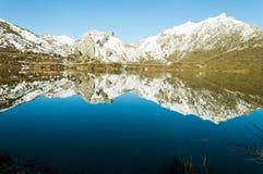 Las colinas cubiertas con nieve se reflejan en un lago en León, España, en una tarde hermosa del invierno fotos de archivo
