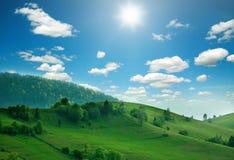 Las colinas de la montaña y los campos verdes en luz del sol en el cielo se nublan Fotografía de archivo libre de regalías