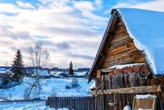 Las colinas Nevado en el campo ruso por mañana, las ventanas de madera rojas de la casa dieron vuelta al este Foto de archivo