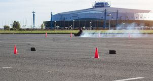 Las competencias de Karting, conductor karting conducen un kart contra la perspectiva de un edificio moderno, mucho humo, ganador imagen de archivo libre de regalías