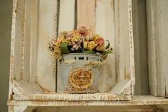 Las composiciones secadas de las flores en metal bucket en la caja de madera blanca Foto de archivo
