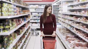 Las compras atractivas en el supermercado, steadicam de la mujer tiraron almacen de video