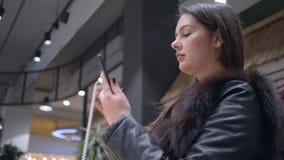 Las compras, cliente femenino en la ropa de la piel eligen y teléfono móvil moderno de prueba en tienda de la electrónica almacen de video