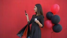 Las compras de Internet, muchacha sonriente feliz hacen compras en línea usando el teléfono móvil y el dinero electrónico en vier almacen de video