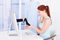 Las compras de la empresaria calzan en línea en el escritorio del ordenador Imágenes de archivo libres de regalías