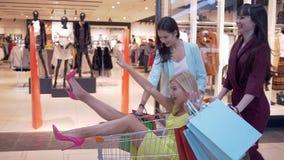 Las compras divertidas, las novias alegres montan en las carretillas de los clientes con las porciones de panieres mientras que l almacen de video