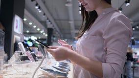 Las compras en tienda de la electrónica, muchacha hermosa utilizan la última tableta moderna y piensan en la compra almacen de metraje de vídeo