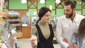 Las compras felices de la familia en un supermercado grande, eligen el pan y los dulces almacen de video