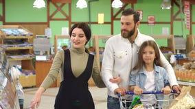 Las compras felices de la familia en un supermercado grande, eligen el pan y los dulces almacen de metraje de vídeo