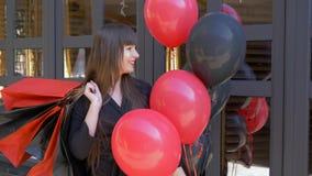 Las compras felices, muchacha de moda con los labios rojos celebran los globos y la porción de paquetes en la calle metrajes