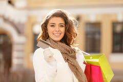 ¡Las compras hicieron fácil! Mujeres jovenes hermosas que sostienen una tarjeta de crédito Foto de archivo