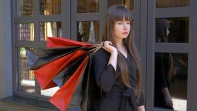 Las compras, retrato de la muchacha seria con los labios rojos en ropa negra celebran la porción de paquetes con las compras y mi almacen de metraje de vídeo