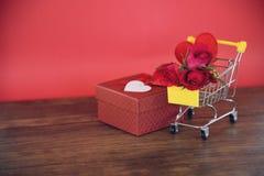 Las compras y las rosas de día de San Valentín florecen la caja de regalo/el carro de la compra llenos con el corazón rojo fotos de archivo libres de regalías