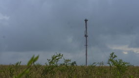 Las comunicaciones de la torre sobre un fondo de las nubes de tormenta asaltan metrajes