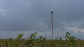 Las comunicaciones de la torre sobre un fondo de las nubes de tormenta asaltan almacen de metraje de vídeo