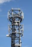 Las comunicaciones Mast contra un cielo azul Imagen de archivo libre de regalías