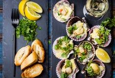 Las conchas de peregrino cocidas en pizarra con el limón, cilantro, empanan el vino blanco fotos de archivo libres de regalías