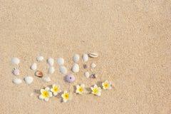 Las conchas marinas del amor de la inscripción del fondo en enarenan con el frangipani del plumeria de las flores Fotografía de archivo libre de regalías