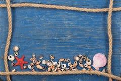 Las conchas marinas, las estrellas de mar y una cuerda formaron el marco en un fondo de p Fotos de archivo