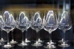 Las copas de vino de cristal se colocan en fila Imagen de archivo libre de regalías