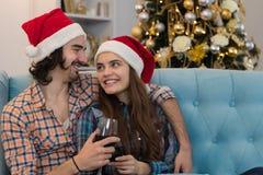 Las copas de vino felices del control de los pares del día de fiesta de la Navidad llevan el Año Nuevo Santa Hat, sonrisa de la m Fotos de archivo libres de regalías