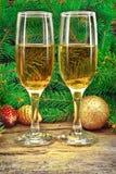 Las copas de vino, la Navidad juegan, cerca de árbol del Año Nuevo Foto de archivo