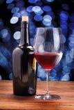 Las copas de vino rojas en la tabla de madera, bokeh del fondo circundan Fotos de archivo