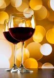 Las copas de vino rojas en la tabla de madera contra bokeh de oro encienden el fondo Foto de archivo
