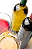 Las copas de vino rojas y blancas acercan a las botellas de vino Fotografía de archivo libre de regalías
