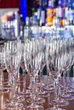 Las copas de vino vacías con color empañan el fondo en barra Imagen de archivo libre de regalías