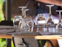 Las copas de vino vacías en la tabla sirvieron para el almuerzo, cena en café Imagen de archivo libre de regalías