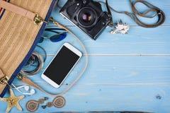 Las cosas femeninas del viaje del verano sobre azul tropical texturizaron el fondo de madera Fotografía de archivo