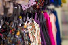 Las cosas son ropa en suspensiones en una tienda de moda de la ropa Ropa en una suspensión en un boutique de la moda Foco selecti imagenes de archivo
