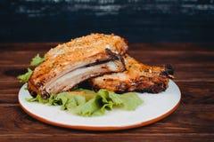 Las costillas de cerdo asadas a la parilla deliciosas sirvieron en lechuga en un viejo tablero de madera rústico Imagen de archivo