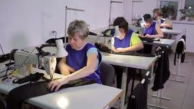 Las costureras están trabajando en el mismo cuarto almacen de metraje de vídeo