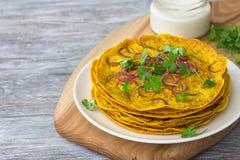Las crepes con la cebolla, el curry y el yogur sauce en una tabla de madera Foto de archivo