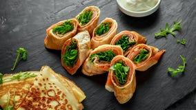 Las crepes de los crespones ruedan con el salmón ahumado relleno con el relleno salvaje de la ensalada de cohete servido en el ta Fotos de archivo
