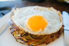 Las crepes de patata con los huevos fritos se sirven con un cuchillo y una bifurcación En la tabla de roble Café por el mar Fotografía de archivo libre de regalías