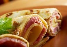 Las crepes rodadas rellenaron el jamón y el queso. Fotos de archivo