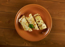 Las crepes rodadas rellenaron el jamón y el queso. Imagen de archivo libre de regalías
