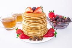 Las crepes sabrosas del desayuno con mora de la fruta, de las fresas y de las zarzamoras vierten la miel del jarabe en un fondo b imagen de archivo libre de regalías