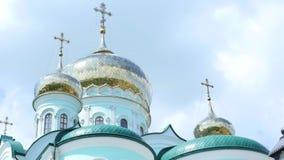 Las cruces ortodoxas del este en el oro cubren con una cúpula las cúpulas contra el cielo nublado azul almacen de video