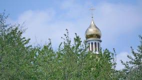 Las cruces ortodoxas del este en el oro cubren con una cúpula las cúpulas contra el cielo nublado azul metrajes
