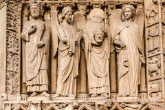 Las cuatro estatuas grandes del lado izquierdo del portal de la Virgen representan un rey y Saint Denis no identificados imágenes de archivo libres de regalías