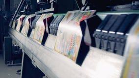 Las cubiertas de papel coloridas están siendo transportadas por una máquina industrial almacen de metraje de vídeo